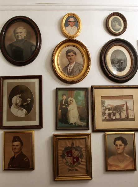 Framed photos of various members of Beth Anderson's family hang on a wall near the entrance to her apartment.