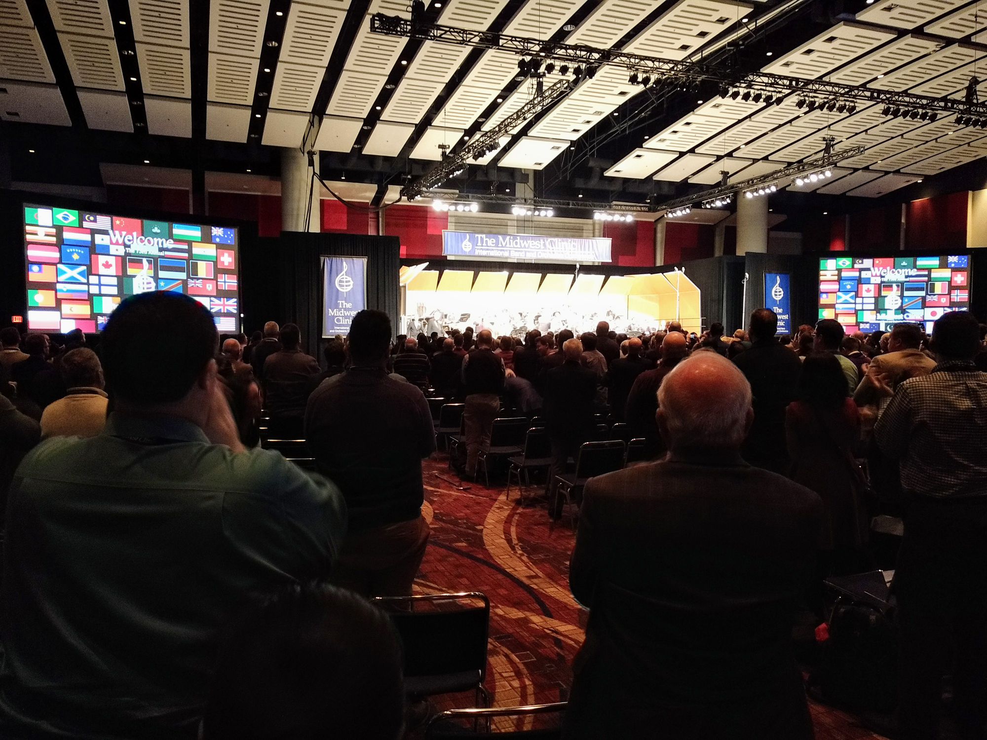 The audience applauding at the conclusion of a wind band concert at the 2019 Midwest Clinic at McCormick Place in Chicago. Signage includes a composite image of flags from all over the world reflecting the nationalities of this year';s performing ensembles.