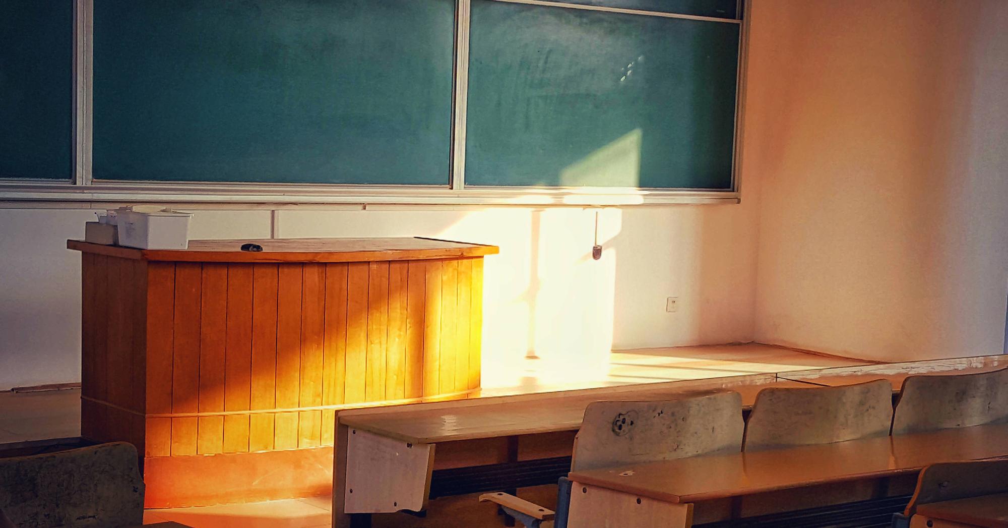 Photo by Barry Zhou (via Unsplash) of a blackboard, teacher's desk and students' desks in an empty classroom with sunlight streaming on the teacher's desk.